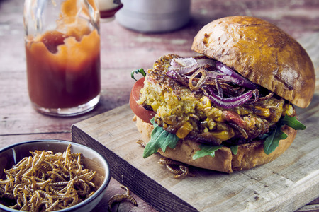 Freshly made insect burger with fried mealworms and salad trimmings served with tomato ketchup and a bowl of crispy crunchy worms to the side on a rustic wooden board