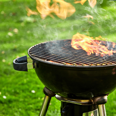 Hot fire burning in a kettle grill barbecue with fiery orange flames shooting above the grill grid in a cropped close up view on green grass