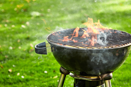 Barbecue fire flaming in a portable barbecue outdoors on a green lawn with empty grill as the fire burns down to coals for cooking