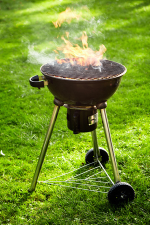 Flaming hot fire burning in a portable BBQ outdoors on a lush green lawn with an empty grill in a close up side view