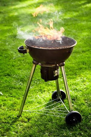 火焰状热火烧在一个便携式的bbq户外在有一个空的格栅的一个豪华的绿色草坪在关闭侧视图