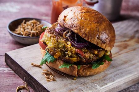 Spezialitäten-Gourmet-Frittierter Mehlwurm-Insekten-Burger mit Salatzutaten auf einem frischen knusprigen Brötchen, serviert auf einem Holzbrett in Nahaufnahme für ein Menü
