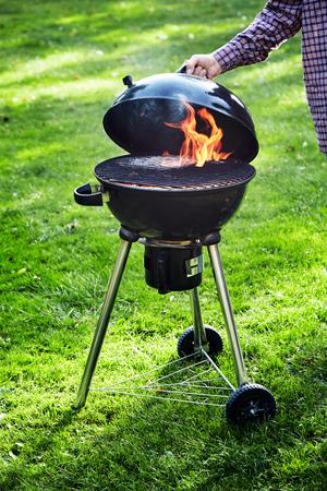 石炭が緑の草の上で屋外で食べ物を調理し始める準備ができているかどうかを確認するために、ケトルグリルでポータブルバーベキュー火災のふたを持ち上げる男