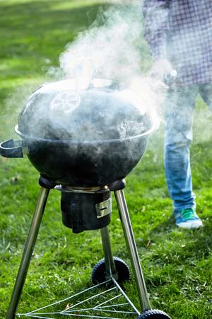 有站立啤酒旁边的啤酒的人等待火的烧烤燃烧到烹调在豪华的绿色夏天草的热的煤炭