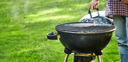 Man checking on the hot coals in a portable BBQ outdoors on a green lawn with copy space in panorama banner format