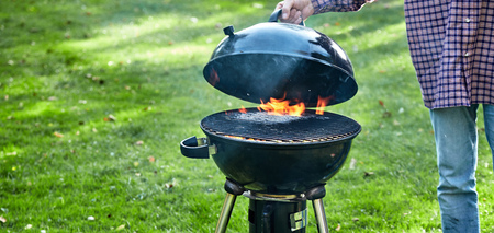 Person lifting the lid on a fire in a portable BBQ to check whether the wood has burned down to hot coals for cooking outdoors on lush green grass in a panorama banner Stock Photo
