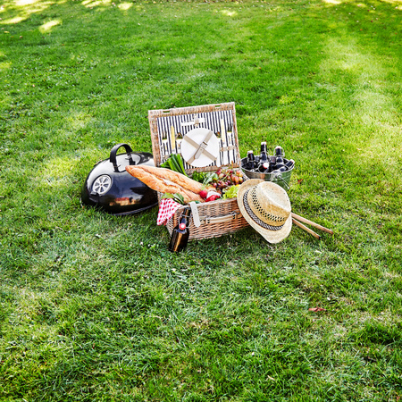 Vintage style summer picnic hamper with fresh vegetables, bunches of grapes and bottles of beer in a silver cooler with French baguettes on a green lawn with copy space in square format