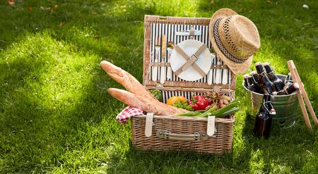 Picnic basket filled with several foodstuffs including baguettes and vegetables next to bucket of bottles Banque d'images - 124857558