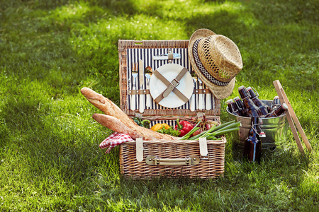 Vintage wicker picnic hamper filled with fresh vegetarian food and French baguettes beside a silver wine cooler with beers on green summer grass