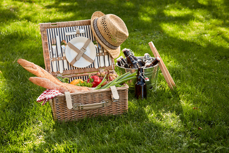Vintage style summer vegetarian picnic in a wicker basket with old straw hat and cooler of beer bottles to the side on lush green grass outdoors