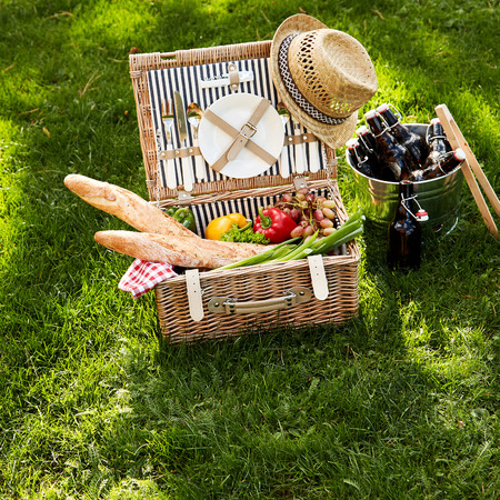 Healthy vegetarian summer picnic hamper with assorted fresh vegetables, French baguettes and grapes alongside a silver wine cooler filled with bottles of beers on lush green grass