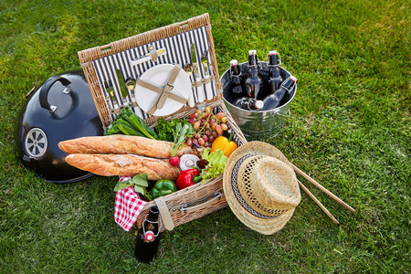 Vintage style wicker picnic hamper with an assortment of fresh vegetables for salads and crusty French baguettes alongside a silver cooler with bottles of beer outdoors on green grass Reklamní fotografie