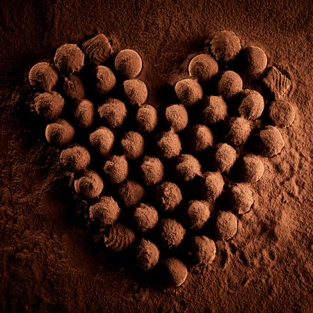 Several confectionery bonbons covered in chocolate dust lying on top of brown cocoa powder in heart shape