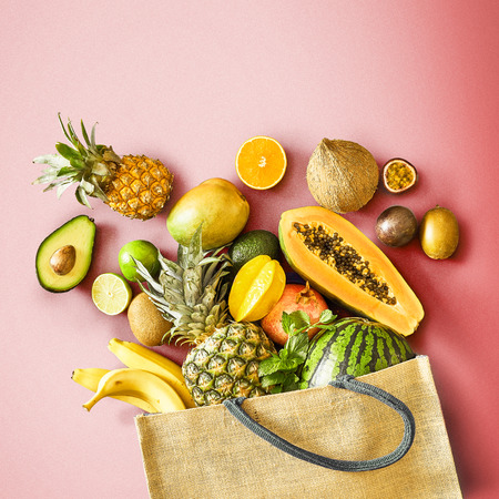 Flat lay still life on a graduated red background of assorted fresh tropical fruit overflowing from a reusable grocery bag in a concept of healthy summer eating and nutrition Reklamní fotografie - 124857568