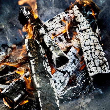 Hot coals and charred logs with small orange flames in a BBQ fire in a close up view ready for cooking the food