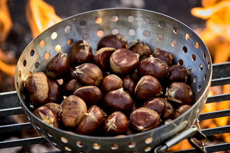 Metal roaster filled with fresh autumn chestnuts roasting on a grill over the hot coals of a barbecue fire Imagens