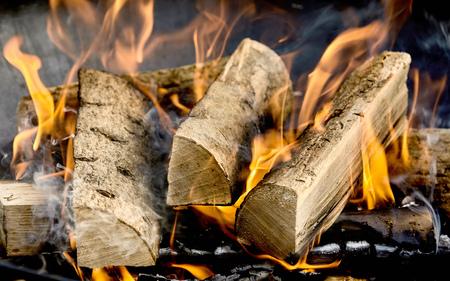 Bûches séchées de bois brûlant dans un barbecue ou un foyer domestique sur un lit de braises avec des flammes orange ardentes dans une vue plein cadre en gros plan Banque d'images