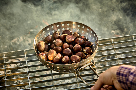 Man roasting a batch of fresh sweet chestnuts on a grill over the hot coals of a barbecue fire in a first person POV