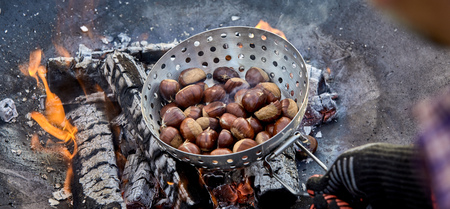 Panorama banner of a man roasting fresh chestnuts in a metal roaster over hot coals of a barbecue fire outdoors in a first person POV