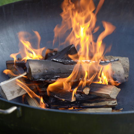 Close up on blazing logs of wood in a portable barbecue with fiery orange flames and chopped kindling below Reklamní fotografie - 124857524