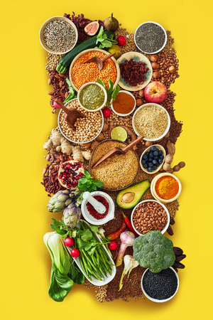 Large assortment of fresh fruit, vegetables and spices with pulses, pomegranate, avocado, artichoke, seeds, endive, fig and lemon on a colorful yellow background framing the food Reklamní fotografie - 124857526