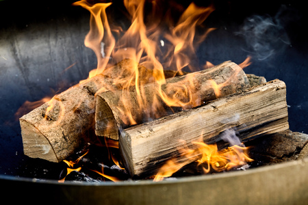 Burning logs flaming in a barbecue fire on a bed of hot coals in a close up view conceptual of an outdoor lifestyle and natural fuel Zdjęcie Seryjne