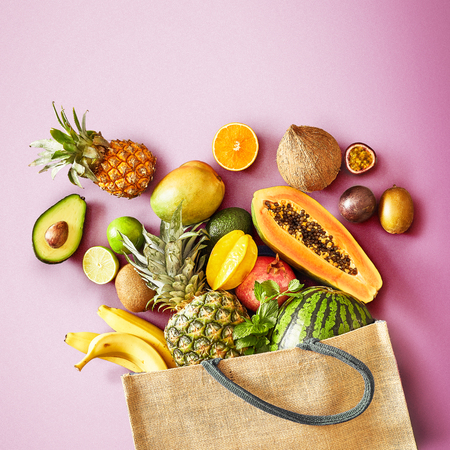 Large variety of fresh tropical fruit on a colorful pink square background spilling from a reusable shopping bag conceptual of a healthy diet and nutrition Reklamní fotografie