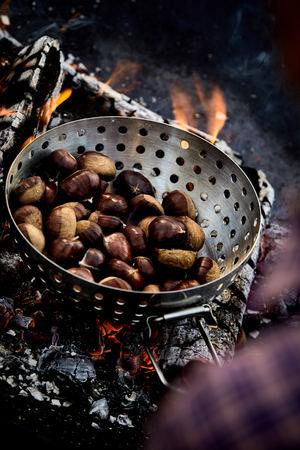 Castañas frescas asadas en un tostador de metal sobre brasas en un fuego de barbacoa para una merienda de otoño saludable Foto de archivo