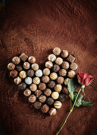 Heart shaped still life of an assorted selection luxury chocolate bonbons on a bed of cocoa powder with a red rose symbolic of love ad romance with copy space above for valentines greeting