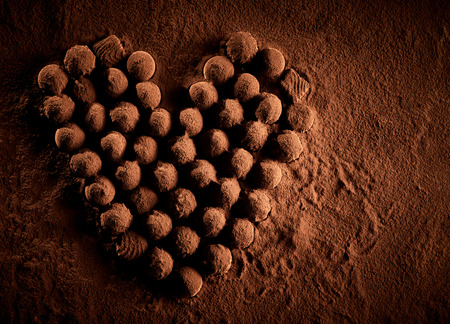 Cocoa powder covered gourmet chocolates placed into heart shaped formation to symbolize romance over brown dust