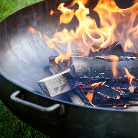 Smoking hot wood fire with fiery flames in a portable kettle grill BBQ outdoors on green grass in preparation for cooking a summer picnic lunch Reklamní fotografie