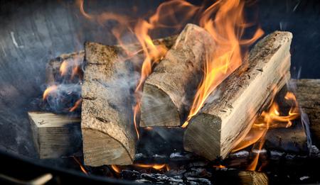 Fuoco acceso di recente con tronchi di legno ardente su un letto di legna tagliata in un barbecue estivo portatile in una vista panoramica ravvicinata del banner