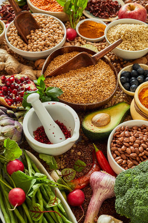 fresh produce and food background with dried pulses in bowls, spice and assorted fresh vegetables in a healthy diet concept in a close up view