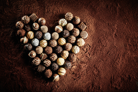 Luxury handmade chocolate pralines in a heart shape symbolic of romance and love on a background of cacao powder with copy space for valentines