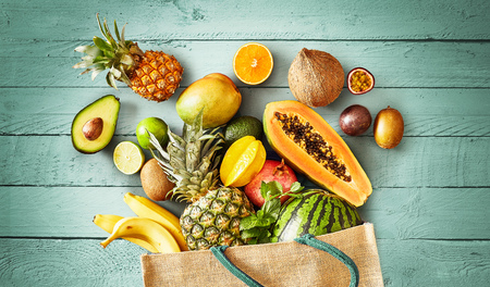 Large selection of fresh tropical fruit spilling from a reusable grocery bag onto green wood in a flat lay still life conceptual of a healthy diet and nutrition