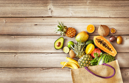 Selection of juicy fresh tropical fruit on a wood panel with copy space overflowing from a reusable shopping bag in a healthy diet concept