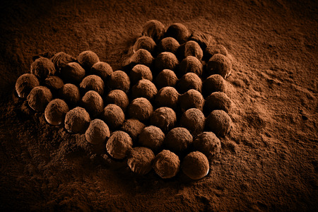Romantic heart shaped arrangement of luxury chocolate balls, bonbons or pralines dusted with cocoa powder viewed low angle for a Valentines card Stock Photo - 124857490