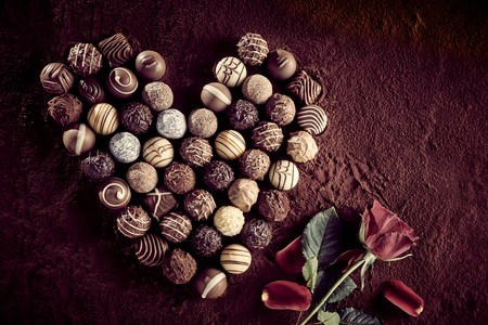 Overhead view of assortment of many small gourmet decorated chocolates next to red rose over brown background Stock Photo