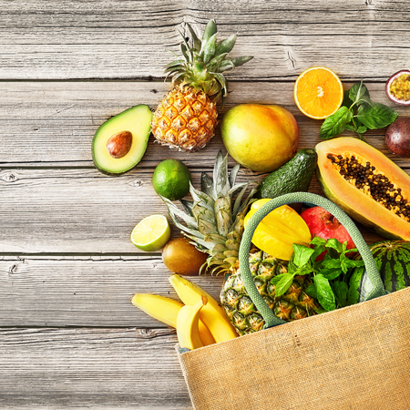 Multiple spilled fruits including pineapple and kiwifruit next to bag over rustic wooden bench background