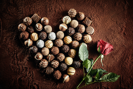 Heart shaped arrangement of assorted luxury handmade chocolates with a single red rose on a bed of cocoa powder symbolic of love, romance and Valentines Day Reklamní fotografie - 124857497