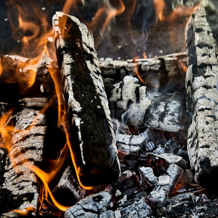 Hot coals and charred burning logs of wood with licking orange flames at the sides in a fire in a close up full frame view