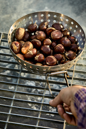 Man roasting fresh sweet chestnuts in their shells in a metal roaster over the hot coals of a barbecue fire in a first person POV with his hand Imagens