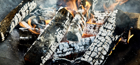 Hot coals and charred logs in a BBQ fire ready for cooking the food in a close up view in a panorama banner