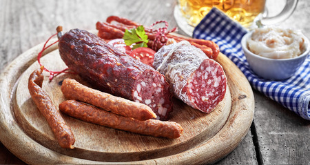 Assortment of spicy dried venison wild boar and deer sausages on a circular board on a rustic table with tankard of beer and bowl of dip or dressing in a close up view for a menu in a panorama banner