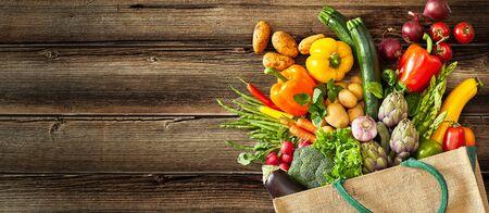 Beige Canvas-Einkaufstasche mit dunkelgrünem Griff, der umgefallen ist, während Gemüse und Obst auf Holzbretter fallen gelassen werden Standard-Bild