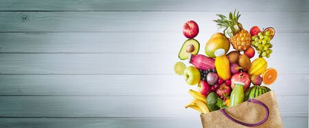 Colorful assortment of healthy fresh tropical summer fruit overflowing from a reusable cloth shopping bag onto a grey wooden panel with highlight and copy space, panorama banner Reklamní fotografie
