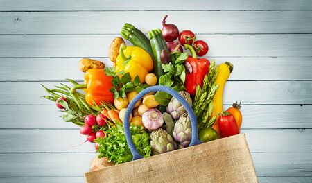 Grocery bag with assorted colorful vegetables and fruits falling out onto light blue wood bench background Reklamní fotografie - 124857412