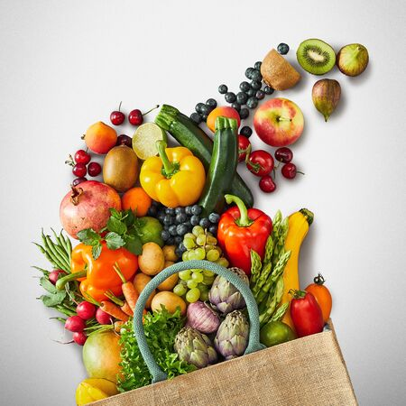 Several fruits and vegetables uncluding pumpkins and artichokes next to reusable grocery bag on top of white background Standard-Bild - 124857176
