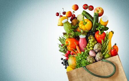 Healthy foods including vegetables and fruits spilling out of canvas grocery bag onto blue and white background