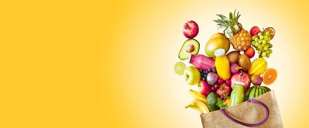 Colorful yellow panorama banner with copy space of a large assortment of fresh tropical fruit and juices rich in vitamins spilling from a reusable grocery bag in a healthy diet concept Stock Photo